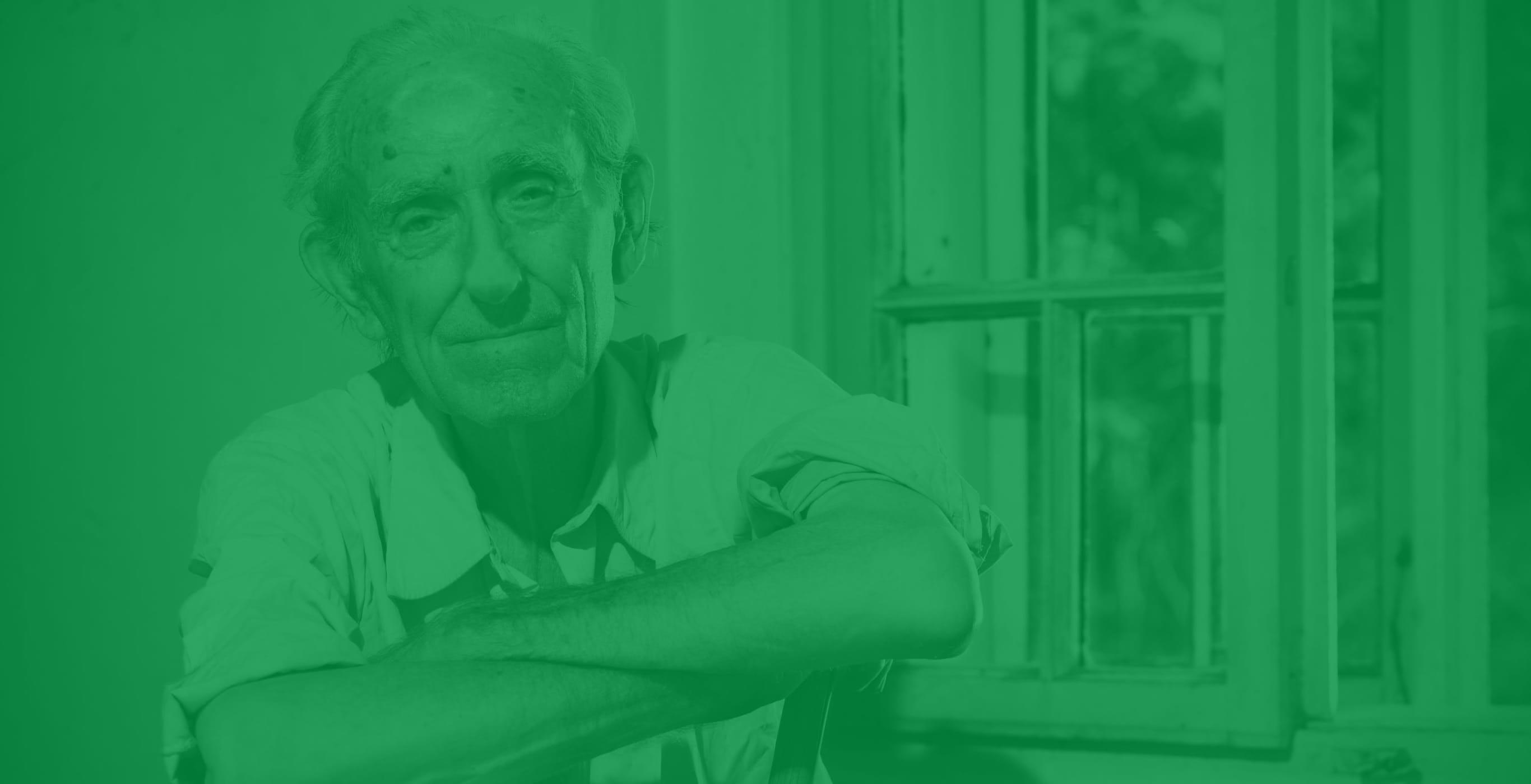 Älterer Mann auf einem Stuhl sitzend lächelt in die Kamera, Motiv eines Website-Launches der Healthcare Werbeagentur mcs