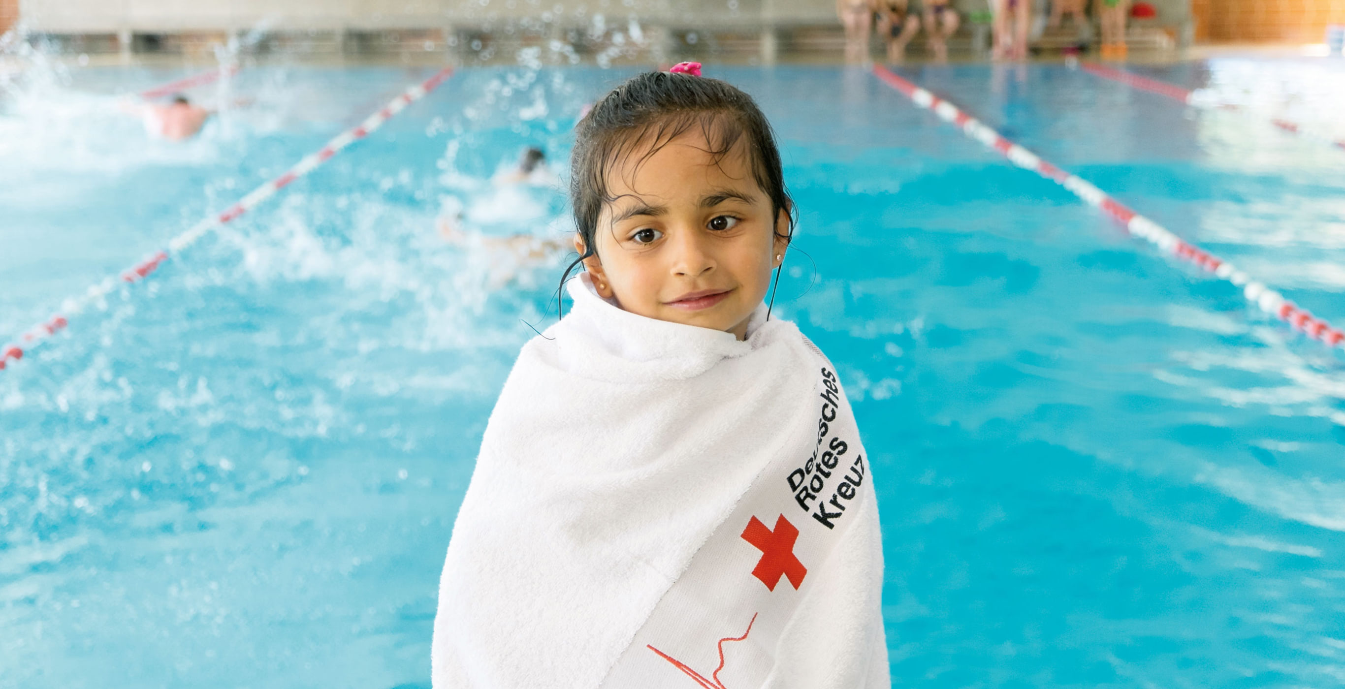 Ein kleines Mädchen sitzt in ein Handtuch gewickelt am Beckenrand im Schwimmbad, ein Motiv auf einer von der Healthcare Werbeagentur mcs gestalteten Website