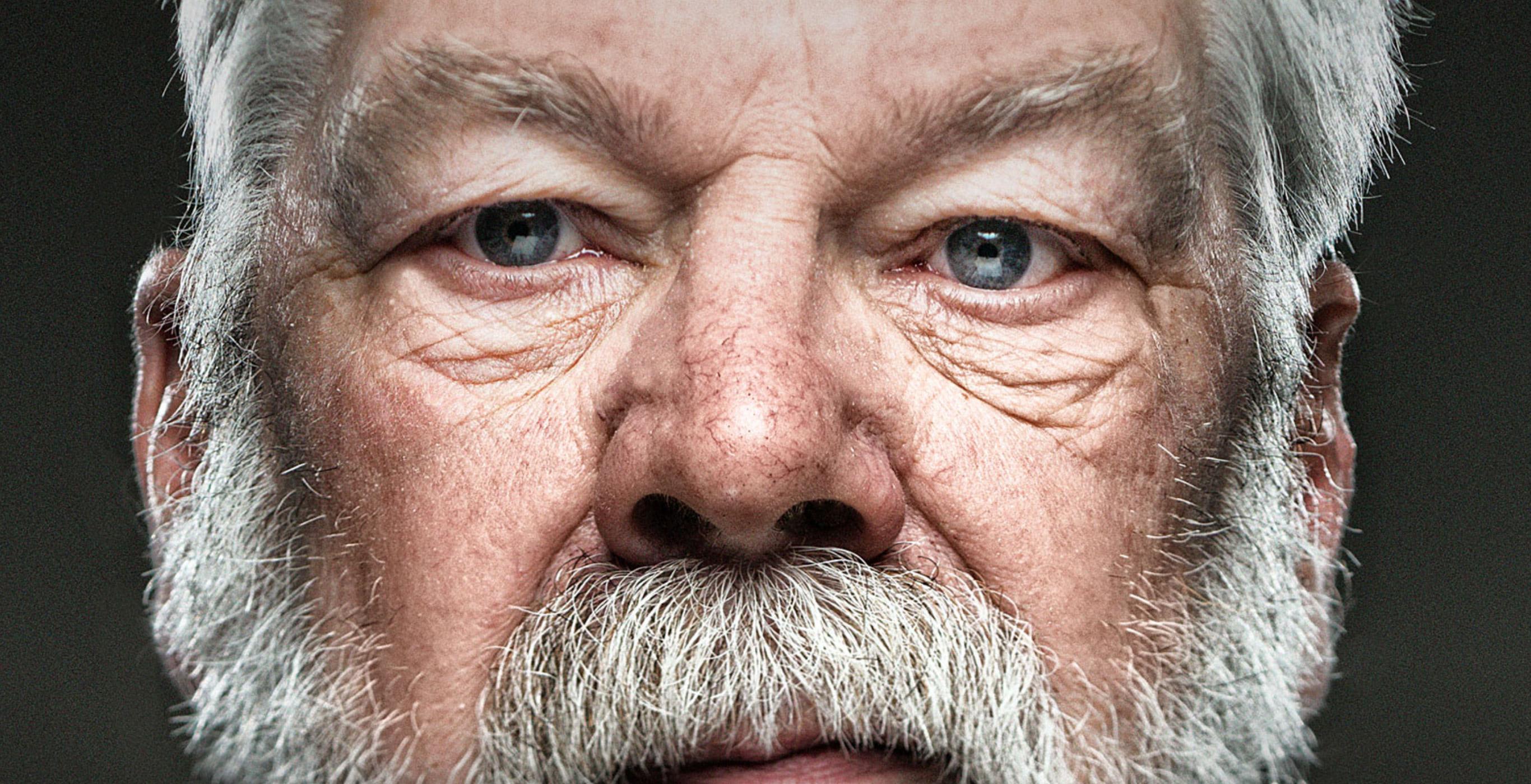 Auf einem Kampagnenmotiv für Personalmarketing der Healthcare Werbeangentur mcs schaut ein älterer Mann geradewegs in die Kamera