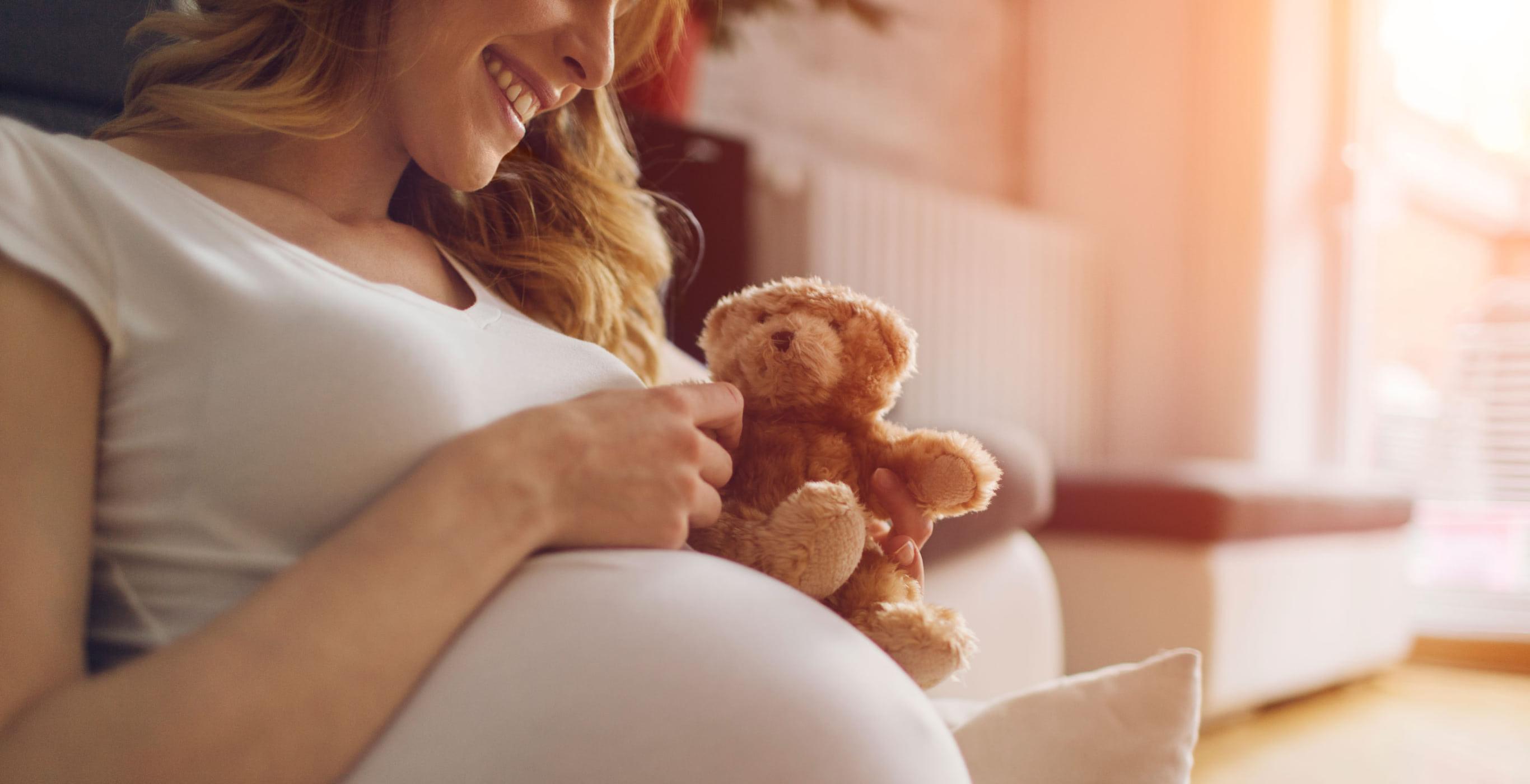 Titelmotiv einer Content-Kampagne der Healthcare Werbeagentur mcs mit einer schwangeren Frau, die einen Teddy in der Hand hält und lächelt